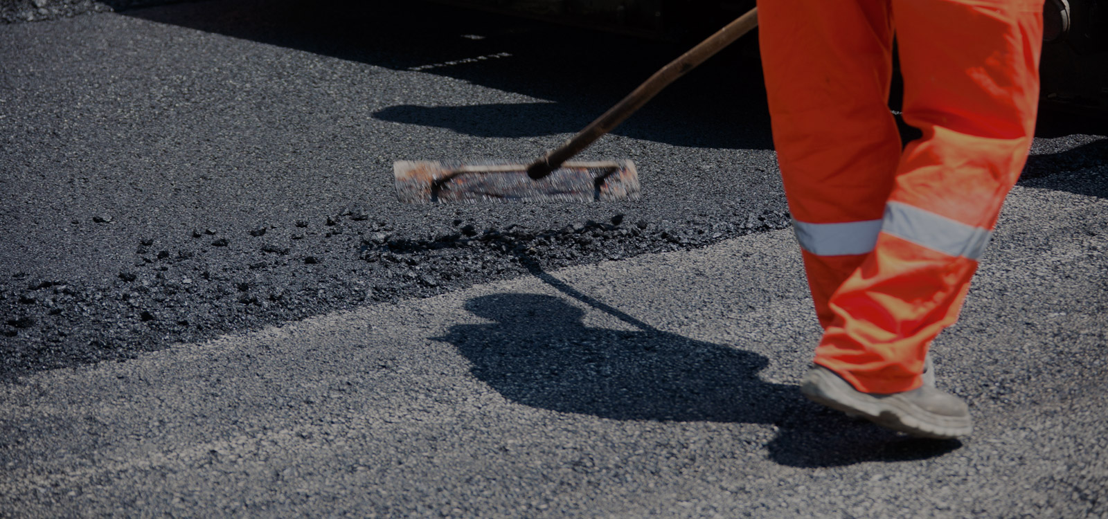 asphalt contractor flattening fresh pavement